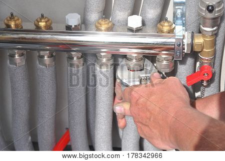 Radiant Floor Heating Installation Heating System. Man install underfloor water heating floor construction. Floor heating installation.