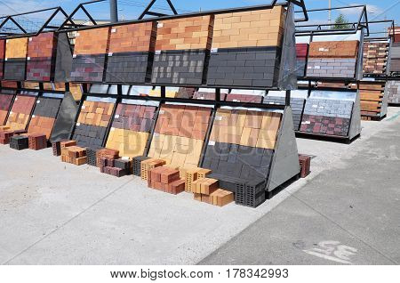 KIEV UKRAINE - March 28 2017:  Stacks of various building and construction materials colored bricks concrete pavers paving stone organized on pallets for sale stored on metal shelves outdoors.