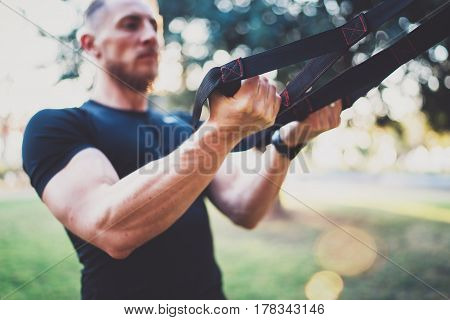 Healthy lifestyle concept.Muscular athlete exercising trx push up outside in sunny park.Great TRX workout.Young handsome man in sportswear doing exercising outdoors.Blurred