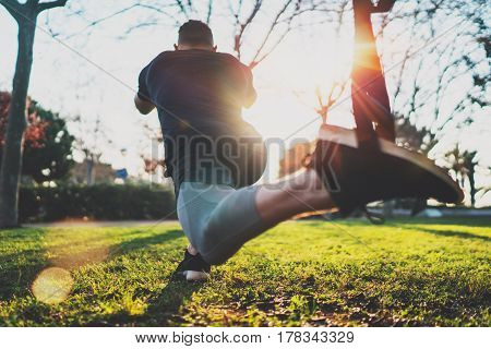 Feel your strength concept.Rear view of young athlete exercising trx outside in sunny park.Great TRX workout.Handsome man in sportswear doing exercising outdoors.Blurred background, flare