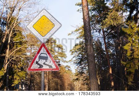 Dirty traffic sign Slippery road in the forest, careful driving in the countryside travel