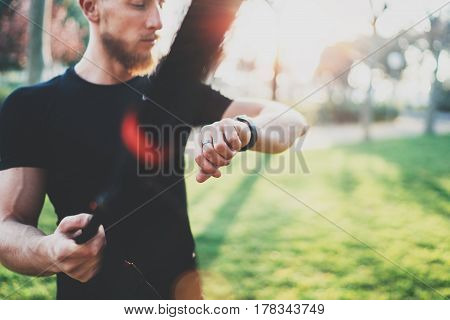 Workout smart lifestyle concept.Bearded muscular athlete doing great exercising TRX outside in summer park.Young handsome man in sportswear checking sport watch tracker.Blurred background, flares
