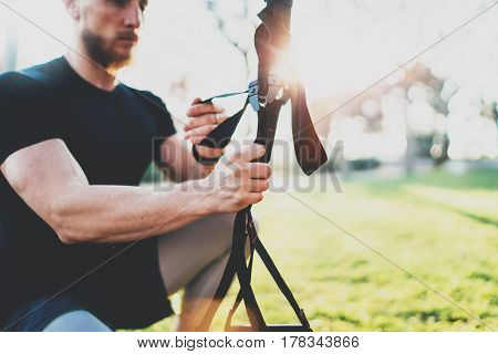 Workout lifestyle concept.Young muscular athlete preparing TRX for exercising outside at summer park.Great trx workout sunny morning.Blurred background, flare