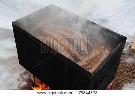 Smoked Fish In Smokehouse Box. Smoked Pike. Fish of hot smoked. Russia.