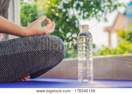 Hand Of A Woman Meditating In A Yoga Pose On A Rug For Yoga And A Bottle Of Water