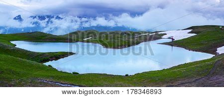 From the green lawn opens panoramic view on a fantastic high mountain lake rocky mountains and beautiful cloudy sky. Happy lifestyle. Beautiful universe.
