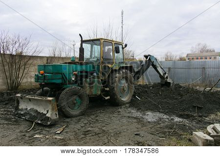 An old Soviet tractor digs and loads waste stone processing near the shop