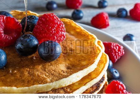 close up of homemade pancakes with fresh berries and honey on rustic wooden background for breakfast