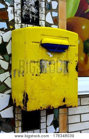 Old yellow mailbox hanging on the brick wall of a house in the village