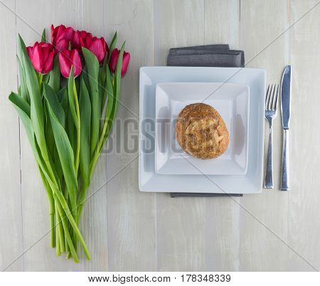 Red tulips next to plates with french dinner roll
