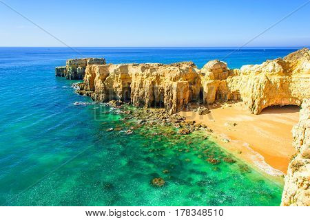 beautiful sea view with secret sandy beach among rocks and cliffs near Albufeira in Algarve Portugal