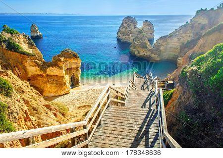 Wooden footbridge to beautiful beach Praia do Camilo near Lagos in algarve region Portugal