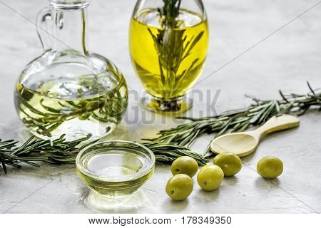 extra oil in carafe with spices and fresh olive on stone desk background