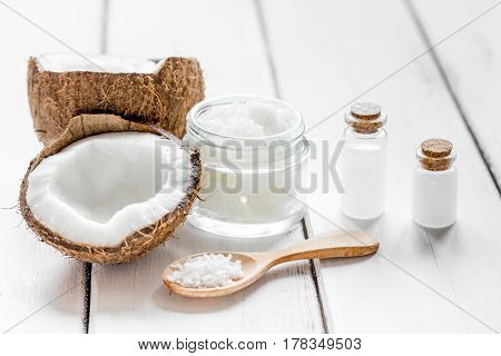 fresh coconut with organic cosmetic oil in glass jar on white background mock up