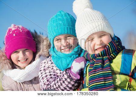 Three happy kids having fun in winter park