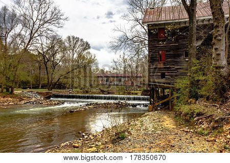 Childersburg Alabama USA - March 25 2017: Springtime at Kymulga Park. Kymulga Grist Mill on the banks of Talledega Creek with the Kymulga Covered Bridge in the background.
