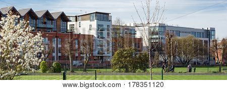 Newbury, UK. 26th March 2017. People are enjoying the sunshine on a sunny spring day in a park in central Newbury. The modern Parkway shopping precinct and apartments dominates the skyline.