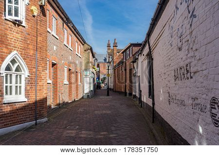 Newbury, UK. 26th March 2017. An old lane by the River Kennet in central Newbury on a sunny spring day. Some people can be seen in the distance towards the main shopping street.