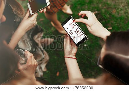 50 percentage big sale concept text. woman looking on 50 percentage big sale text on phone screen and pointing. stylish elegant girls at party celebration in sunny park. advertising