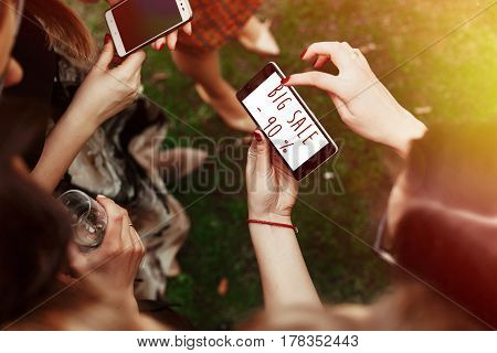 big sale 90 percentage concept text. woman looking on 90 percentage big sale text on phone screen and pointing. stylish elegant girls at party celebration in sunny park. advertising