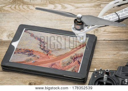 aerial photography concept - reviewing pictures of Colorado foothills with a dry stream on a digital tablet with a drone rotor and radio controller, screen picture copyright by the photographer