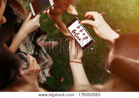 shop online concept text. woman looking on shop online text on phone screen and pointing. stylish elegant girls at party celebration in sunny park. advertising. shopping online. e-commerce