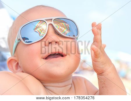 Adorable Happy funny smiling cute baby boy on the beach