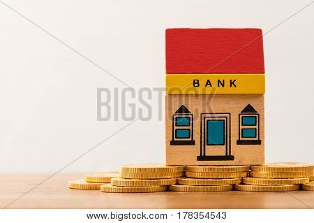 Toy brick bank building sitting on solid gold assets as illustration of too big to fail banks. Repeal of Dodd-Frank could jeopardize the assets of large investment banks