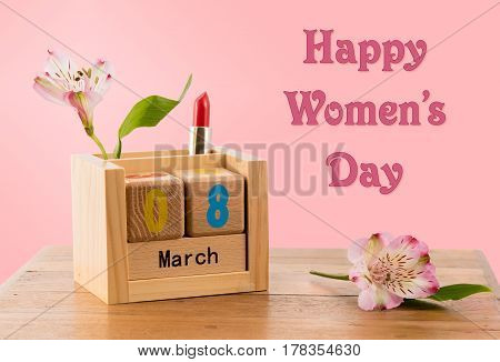 Happy Women's Day or International Womens Day celebrated on March 8th. Pink background image with wooden calendar and blossoms