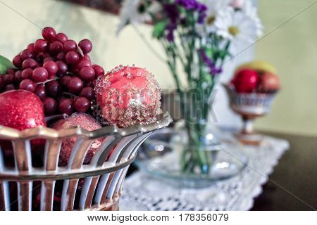 Seasonal, Festive Display:  A seasonal display of decorative apples and grapes in a ceramic basket. Appropriate background layer for Christmas cards and seasonal advertising.