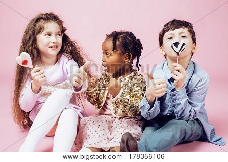 lifestyle people concept: diverse nation children playing together, caucasian boy with african little girl holding candy happy smiling close up