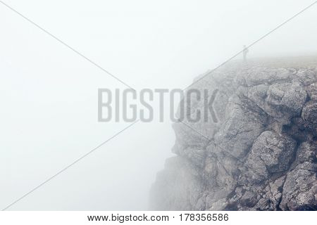 Man trekking in mountains. Cold weather, fog and clouds. Winter hiking.
