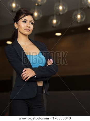 Attractive business woman standing with arms folded making decision