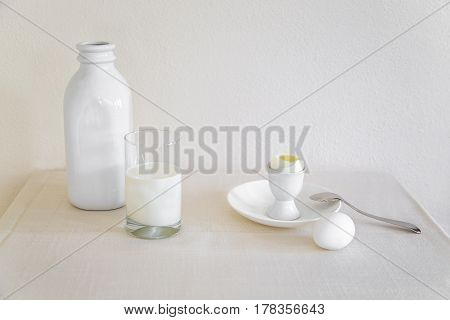 Bottle and glass of milk with eggs on a table with a white tablecloth