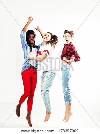three pretty young diverse nations teenage girl friends jumping happy smiling on white background, lifestyle people concept close up