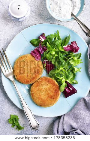 Salmon Patties With Mix Salad Leaves And Yogurt Sauce.top View.