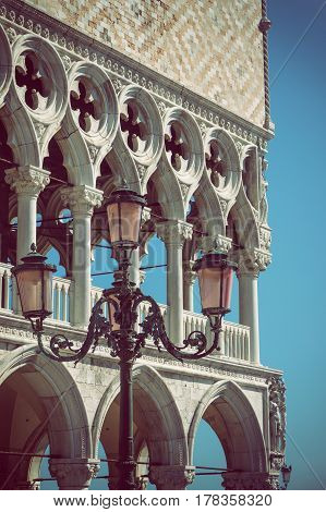 Detail of columns and lamp of the Doge`s palace in Venice (Italy) with blue sky in the background. Edited as a vintage photo with dark edges. Vertically.