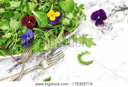 Healthy food. Detox. Organic nutrition. Salad leaves with herbs and flowers