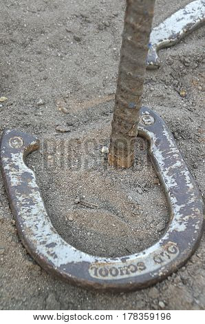 A horseshoe lays around the post scoring a ringer in the game of Horseshoes