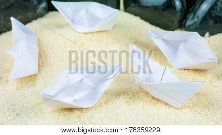 Paper Ships Chaotic Laying on Sandy Bottom without Water .