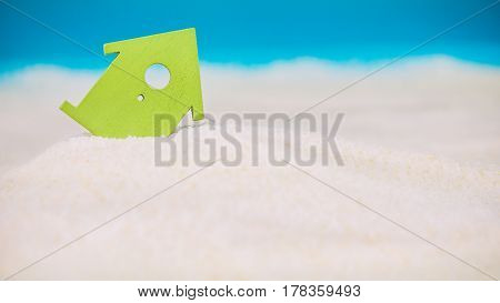 Symbol House Built on Sand, Small Green Symbol of an House Sinking into the Sand, concept of risk in real estate financing