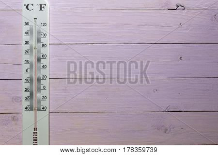 thermometer Celsius and Fahrenheit on a wooden wall