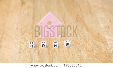 HOME word of cube letters in front of lilac coloured house symbol on wooden surface.