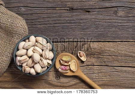Pistachios nuts in bowl and spoon on old wooden background top view