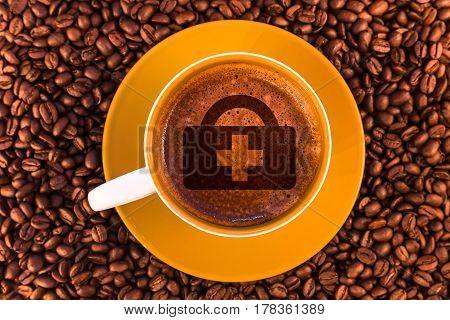 first aid symbol on fresh espresso with a beautiful crema and strewn mediumly roasted coffee beans