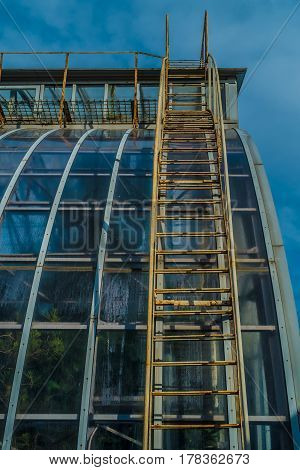Steampunk industrial glass building stairway with a blue  sky on a  sunny day