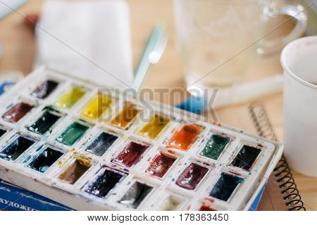Close up of a pallette of watercolor painting paints in a plastic tray.