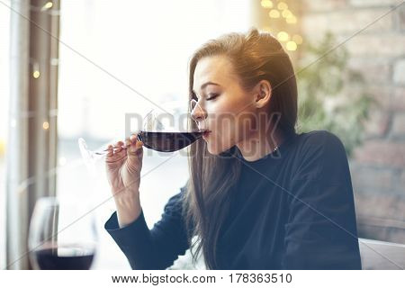 Beautiful young woman drinking red wine with friends in cafe portrait with wine glass near window. Vocation holidays evening concept