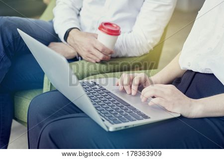 Business meeting in modern office using laptop computer on knees entrepreneur working together on creative project. Focus on keyboard.