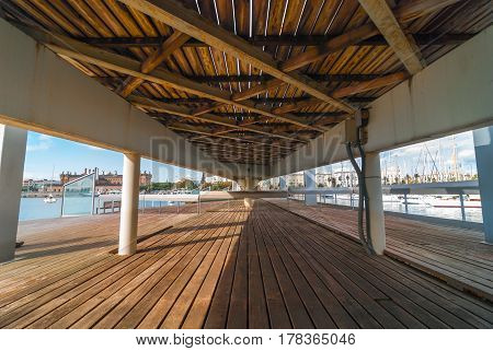 A view toward the shoreline & city waterfront from under the raised pedestrian walkway concourse & bridge at Port Vell marina shopping centre in Barcelona, Spain.